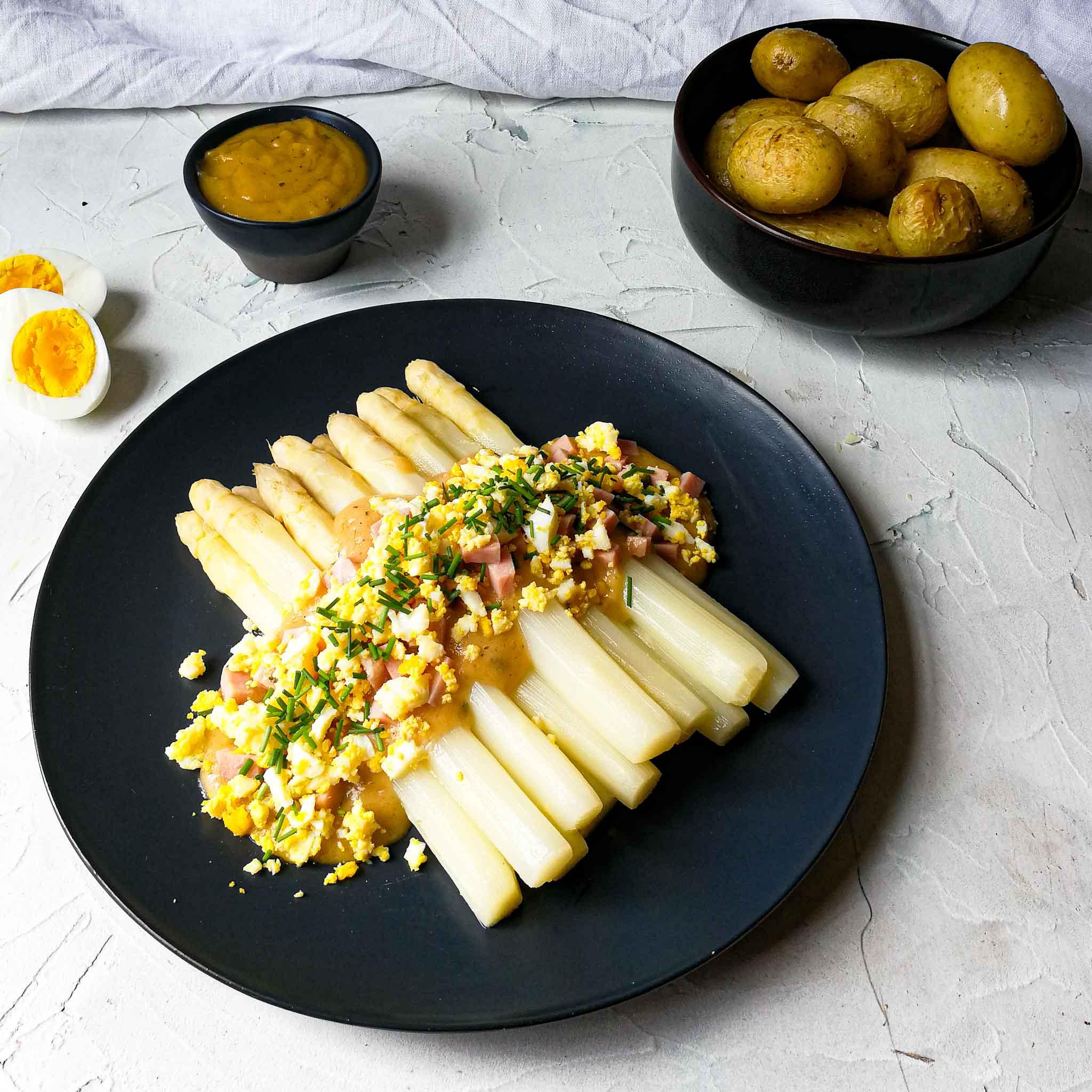 Asperges met ei, ham, botersaus en gepofte aardappel