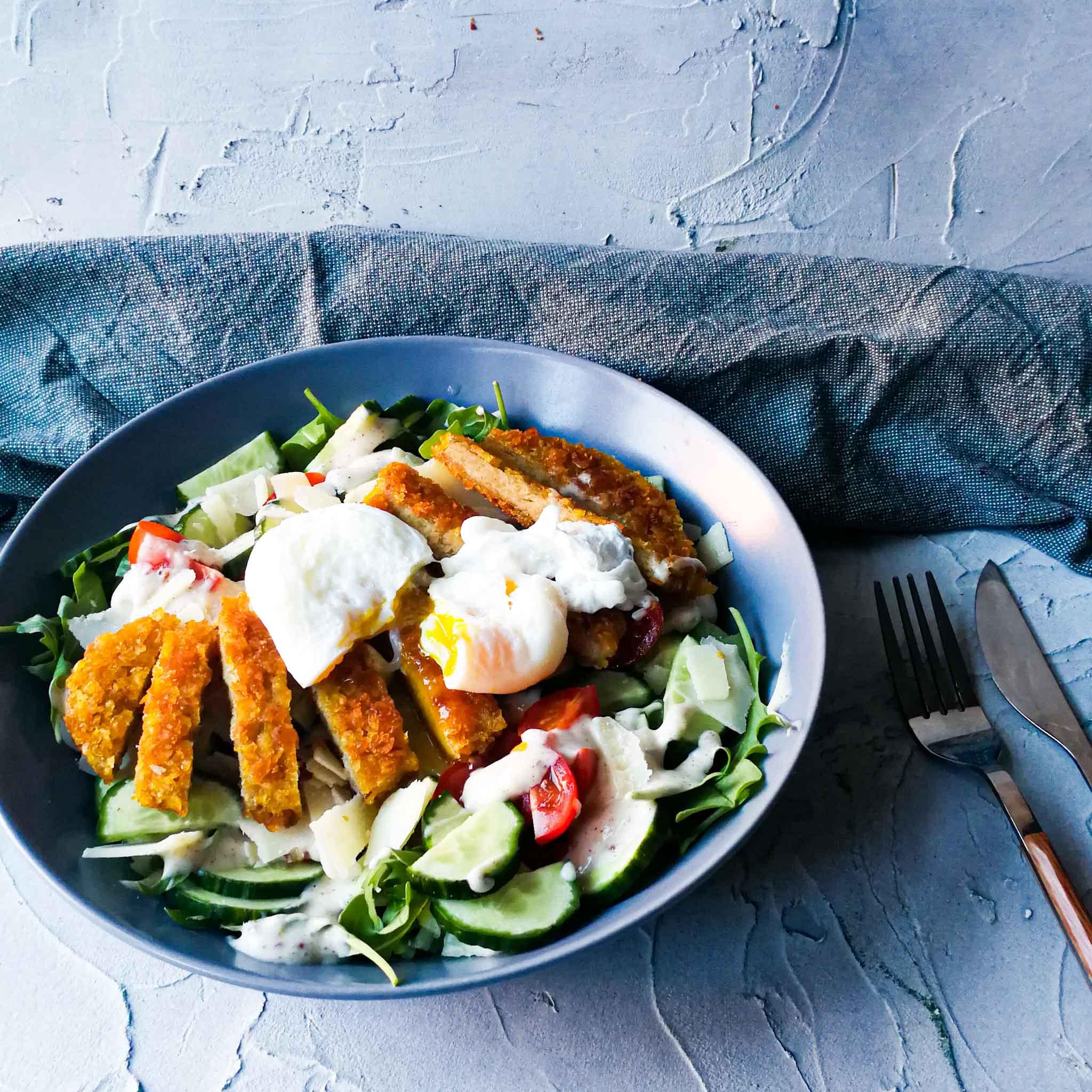 Salade met vega krokante kip en een gepocheerd eitje
